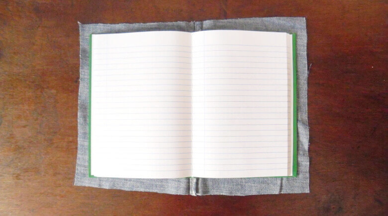 Cut the jean fabric into the notebook size